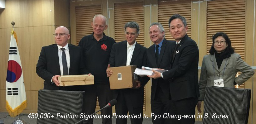 captioned Handing-petition-signatures-to-Pyo-e1485454906624